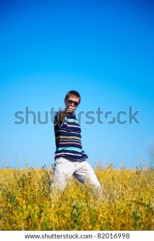 young adult man dances in the field - stock photo