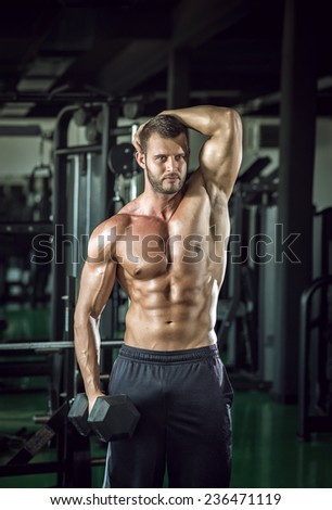 Young adult man doing bicep curls in modern gym. - stock photo