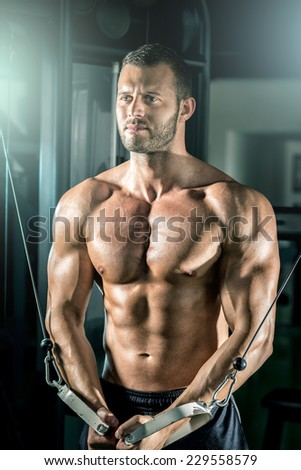 Young adult man doing cable fly in gym. - stock photo