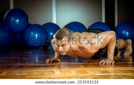 Young adult man doing push-ups in gym. - stock photo