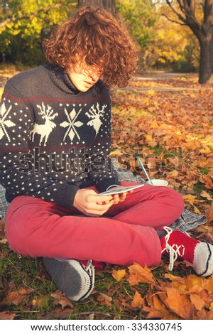 Young adult man dressed in knit sweater with deers, knit shoes and red jeans, have a leisure sitting in autumn park and reading the electronic book. - stock photo