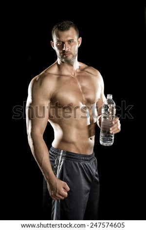 Young adult man drinking water in gym. - stock photo