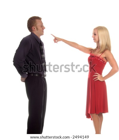 Young adult man facing upset woman with her hand on her hip and pointing at him because she thinks he has forgotten Valentine's Day