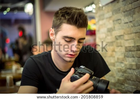 Young adult man holding and looking at professional camera in cafe - stock photo