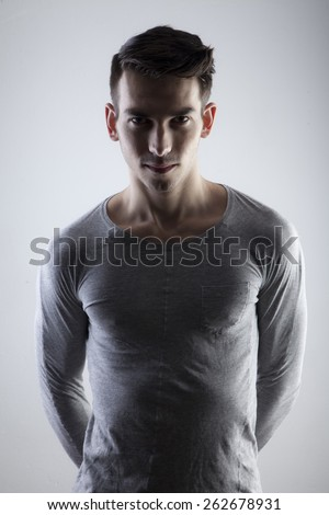 Young adult man in dramatic lighting - stock photo
