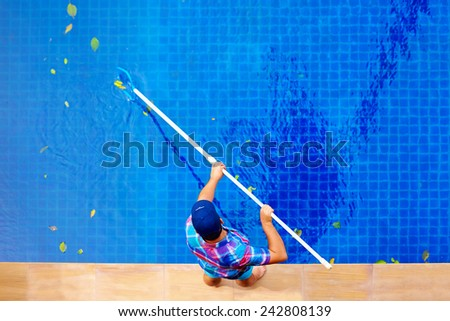 young adult man, personnel cleaning the pool from leaves - stock photo