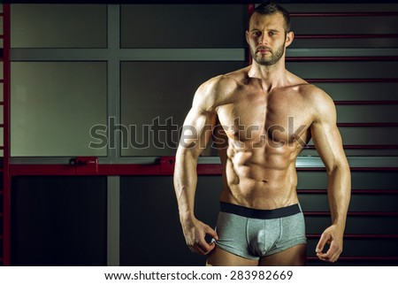 Young adult man posing in pants in gym - stock photo