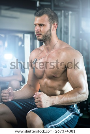 Young adult man sitting in gym and preparing for workout