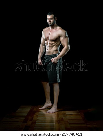 Young adult man standing in gym and posing. - stock photo