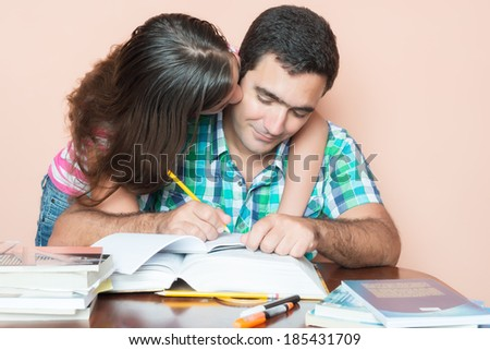 Young adult man studying at home with his daughter hugging and kissing him - stock photo