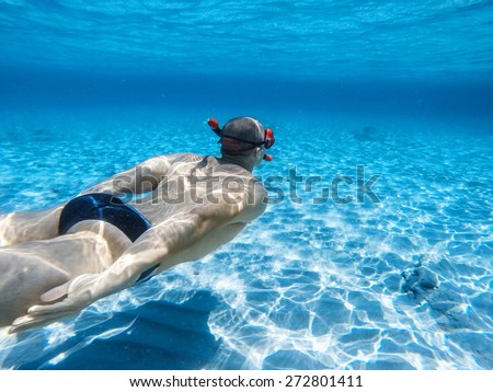 Young adult man swimming in depth of tropical sea water/Man swimming underwater - stock photo