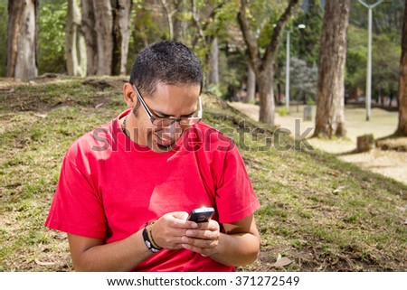 Young adult man using a touchscreen smartphone sitting on a park. - stock photo