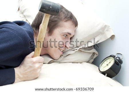 young adult man wake up with clock and hummer, in bad,closeup, - stock photo