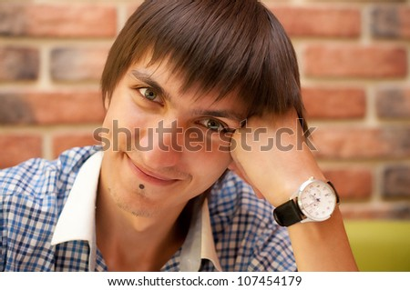 Young adult man with watch sitting at cafe - stock photo