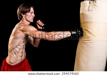 Young adult martial artist with heavy bag. Studio shot over black. - stock photo
