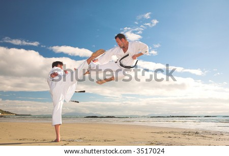 Young adult men practicing Karate on the beach. One is in a high kick and the other flying through the air (some movement on the edges) - stock photo