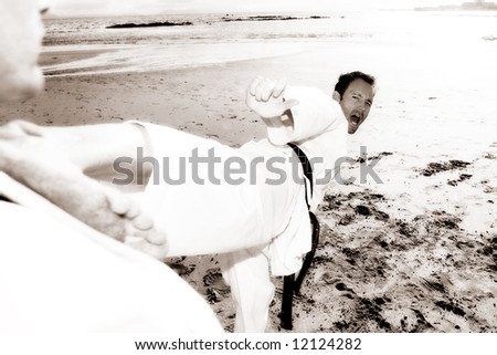 Young adult men practicing Karate on the beach. One is in a high kick on the chest of the other (some movement on the edges) - stock photo