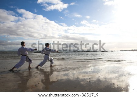 Young adult men with black belt practicing a Kata on the beach on a sunny day. Sunspots and flare from direct sunlight visible - stock photo