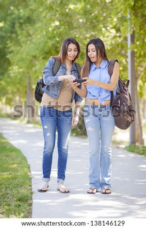 Young Adult Mixed Race Twin Sisters Sharing Cell Phone Experience Outside. - stock photo