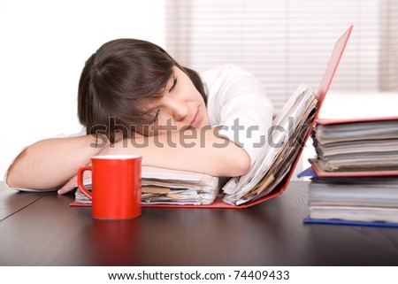 young adult over-worked woman at desk - stock photo