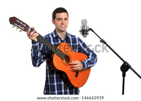 Young adult playing his guitar and singing / Guitar player in action