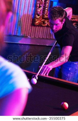 young adult playing pool at nightclub - stock photo