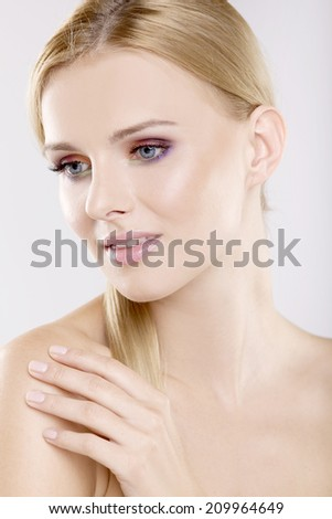 Young adult pretty woman with beautiful blond hairs and multicolor makeup isolated on white background