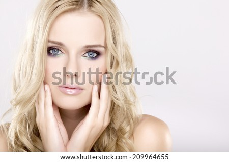 Young adult pretty woman with beautiful blond hairs and multicolor makeup isolated on white background - stock photo