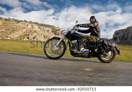 Young adult  rebel biker riding a chopper motorcycle in a remote location