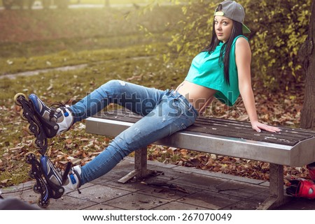 Young adult rollerblade  girl leaning and posing on bench in park. - stock photo