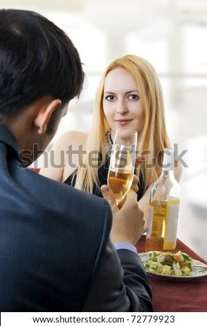Young adult seductive couple at restaurant dining and toasting. - stock photo