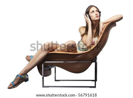 Young adult sitting the chair listening to music - stock photo
