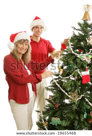 Young adult son helps his mother decorate the Christmas tree.  Isolated on white. - stock photo