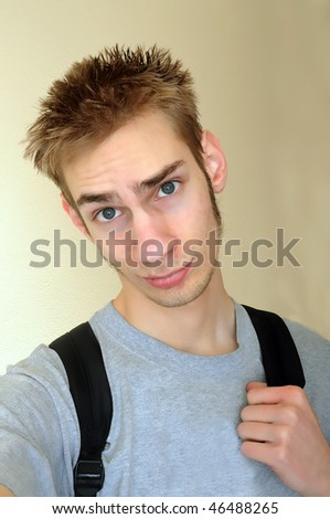 Young adult student smirks with confidence at the camera while holding his hand on his backpack strap. - stock photo