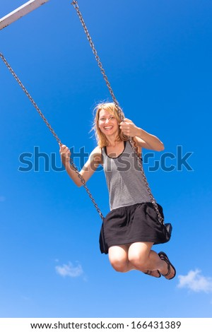 Young adult swings on a swing.