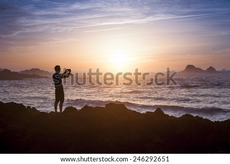 Young adult taking photo of amazing sunset light on the beach