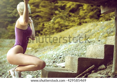 Young adult tattooed woman posing in transparent lingerie on coast of small mountain lake. Toned image. Artistic filters applied. Implicit nudity. - stock photo