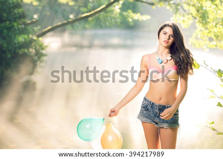 Young adult teen girl posing with balloons on river bank in the spring morning. Toned image. - stock photo