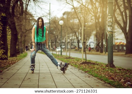 Young adult teenage girl doing roller skating in park during winter - stock photo