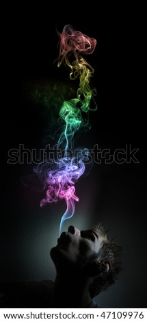 Young adult white Caucasian man smokes in a dark room. The smoke is glowing against the black background and has lots of colors.