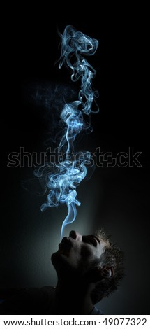 Young adult white Caucasian man smokes in a dark room. The smoke is glowing against the black background - stock photo