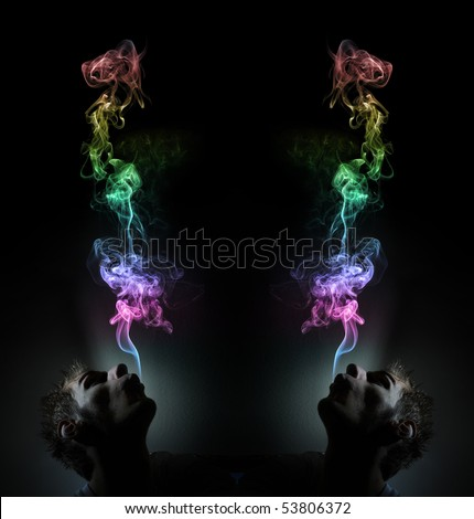 Young adult white Caucasian man smokes in a dark room. The smoke is glowing against the black background and has lots of colors. - stock photo