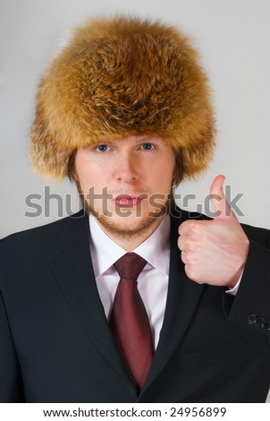 young adult with suit and russian fur hat on grey background - stock photo