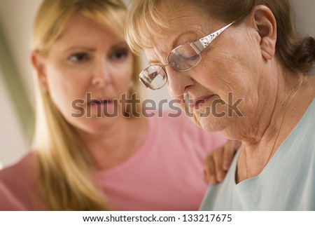 Young Adult Woman Consoles Sad Senior Adult Female. - stock photo