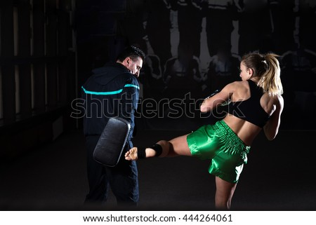 Young adult woman doing kickboxing training with her coach. - stock photo