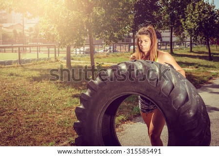 Young adult woman flipping and rolling tire during crossfit exercise outdoor. - stock photo