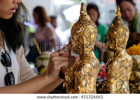 young adult woman gild gold cover leaf to Buddist statue at temple in Visakha Bucha day - the most important memorial day in Buddism, Bangkok Thailand - stock photo