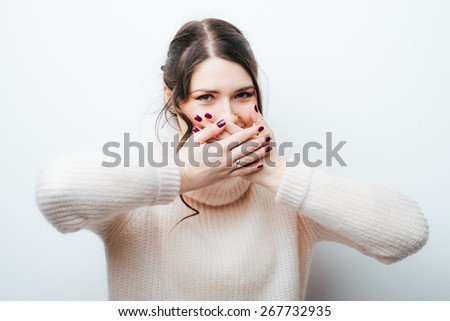 young adult woman holding hand over her mouth over grey background - stock photo