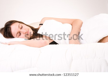 Young adult woman in the studio on a bed