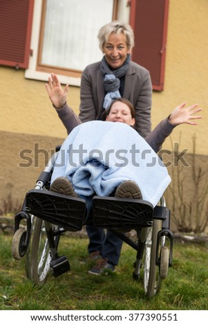 young adult woman in wheelchair, is looking funny, enjoying the live despite her handicap - stock photo